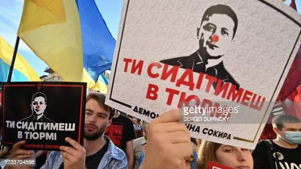 "Demonstrators hold placards depicting Ukrainian President Volodymyr Zelensky reading ""Down with Zelensky!"" and ""Zelensky, you will be jailed soon!""..."