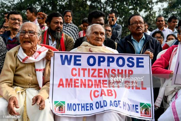 Demonstrators hold placards during a protest against the government's Citizenship Amendment Bill in Guwahati on December 13, 2019. - Internet access...