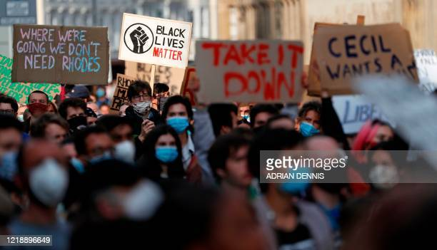 Demonstrators hold placards during a protest arranged by the 'Rhodes Must Fall' campaign calling for the removal of a statue of British businessman...
