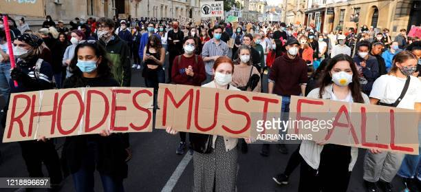 Demonstrators hold placards during a protest arranged by the 'Rhodes Must Fall' campaign, calling for the removal of a statue of British businessman...
