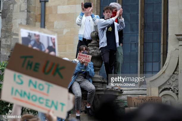 Demonstrators hold placards during a protest calling for the removal of a statue of British businessman and imperialist Cecil John Rhodes, from...