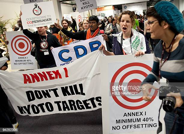Demonstrators hold placards during a protest inside the Bella Center during the Climate Change summit in Copenhagen on December 10 2009 Poor...