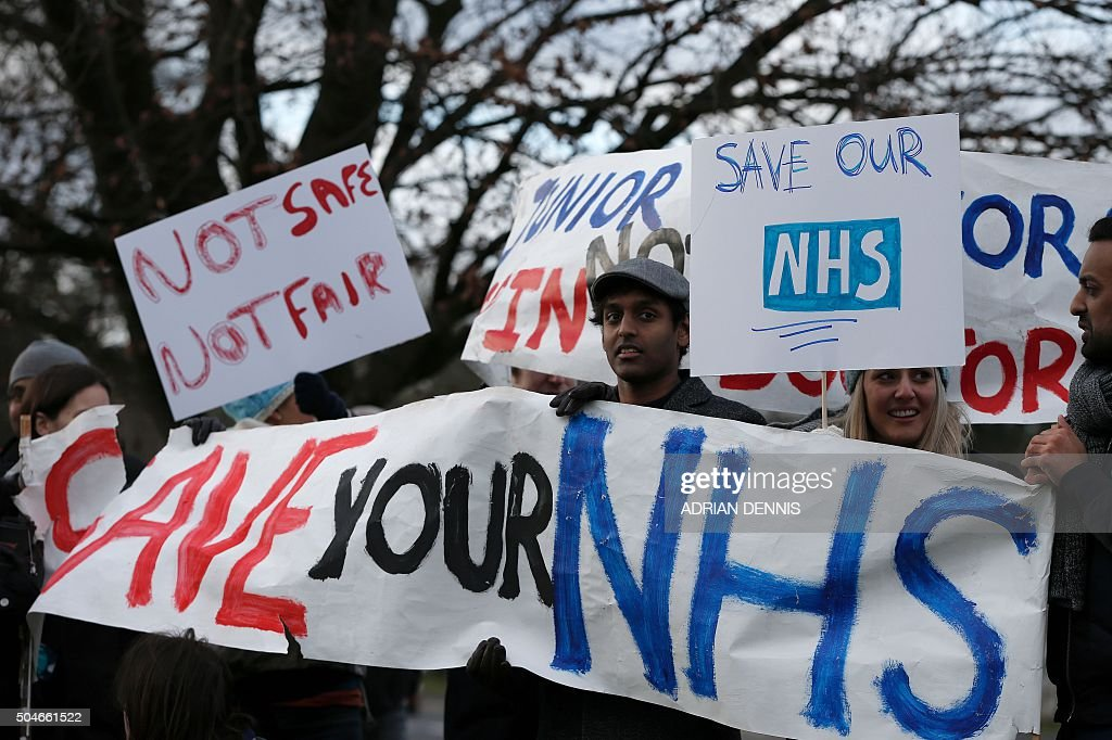 TOPSHOT - Demonstrators hold placards during a protest outside the Frimley Park Hospital in Frimley, south west of London, on January 12, 2016, during a strike by junior doctors. Tens of thousands of junior doctors in England went on strike Tuesday, causing major disruption to hospitals across the country in the first walkout of its kind for 40 years. The strike is over a new type of contract which the government says will improve healthcare at night and at weekends but medics say would drastically reduce their pay.