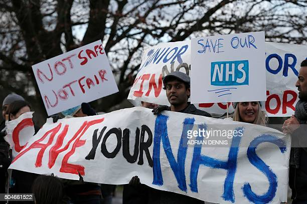 TOPSHOT Demonstrators hold placards during a protest outside the Frimley Park Hospital in Frimley south west of London on January 12 during a strike...