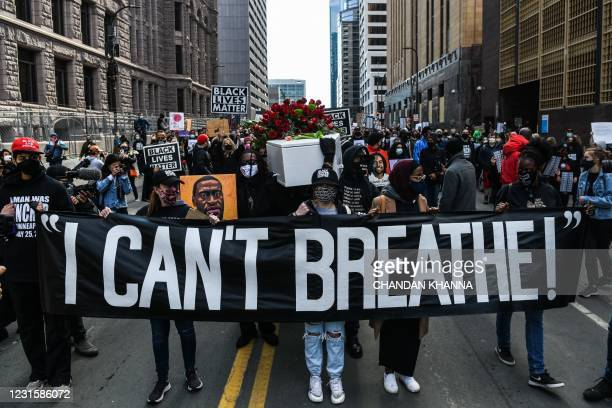 Demonstrators hold placards during the I Cant Breathe - Silent March for Justice in front of the Hennepin County Government Center on March 7 where...
