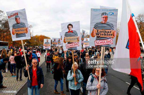 Demonstrators hold placards featuring German Chancellor Angela Merkel, SPD politician Karl Lauterbach and the head of the Robert Koch Institute...