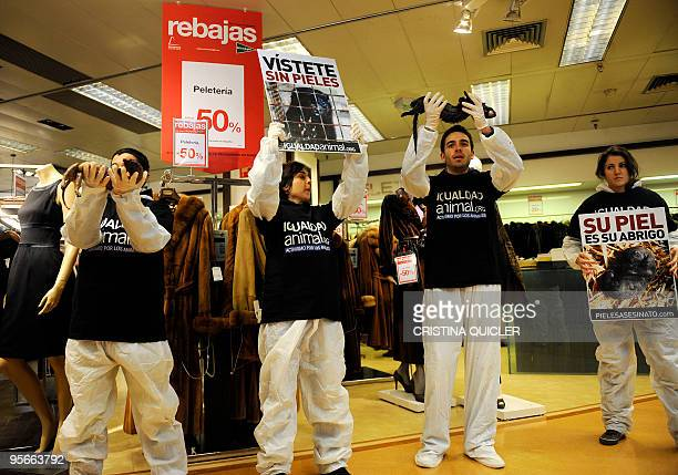 Demonstrators hold placards in a shopping mall to protest against the mistreatment of animals as part of a worldwide day of action to ban the fur...