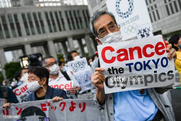 Demonstrators hold placards in front of the Tokyo Metropolitan government building during an anti-Olympic protest in Tokyo, Japan, on Wednesday, June...