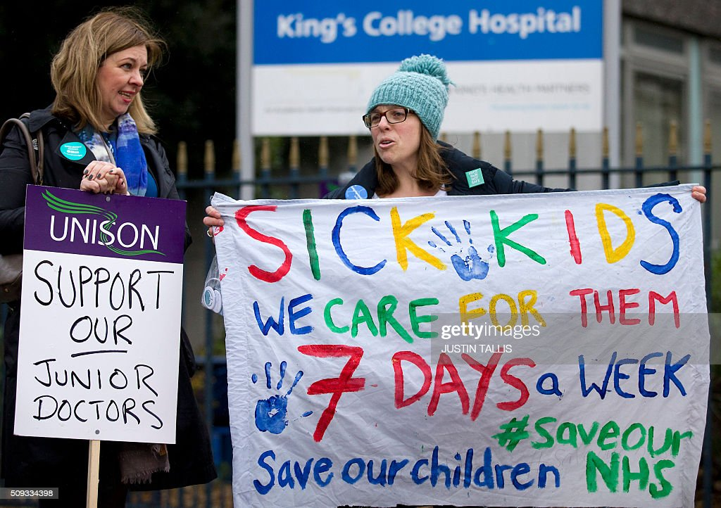 Demonstrators hold placards in support of a 24-hour strike by junior doctors over pay and conditions outside King's College Hospital in London on February 10, 2016. Thousands of junior doctors began a second strike at English hospitals on Wednesday against proposed new working conditions and pay rates. Junior doctors -- all medics below consultant level -- were providing emergency care only from 8:00am (0800 GMT) in the 24-hour strike. / AFP / JUSTIN