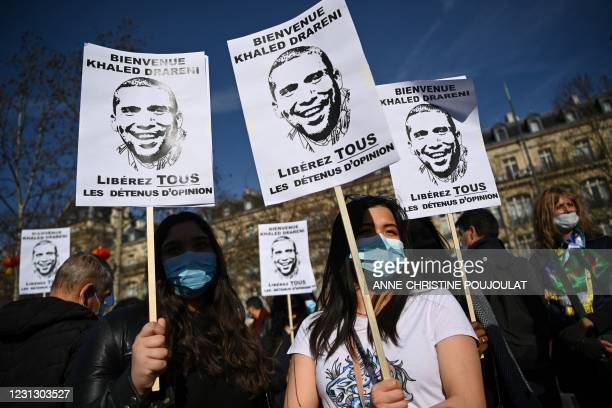 Demonstrators hold placards reading 'Welcome Khaled Drareni, Free all prisoners of conscience' during a rally in Paris on February 21 in support of...