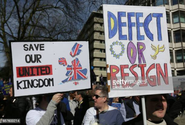 Demonstrators hold placards that read 'Save our United Kingdom' and 'Defect or Resign' as they prepare to participate in an anti Brexit proEuropean...