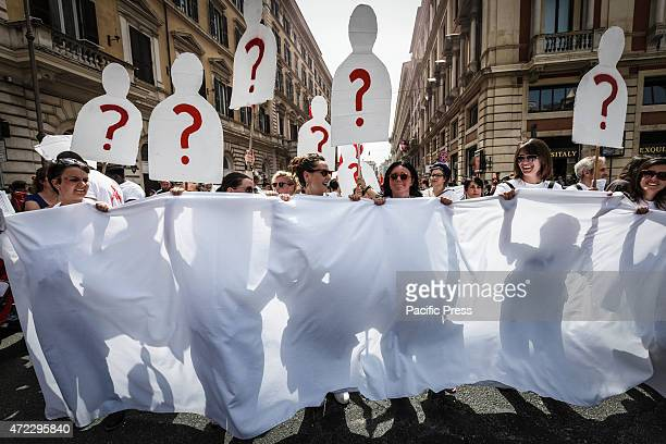 Demonstrators hold placards with a 'question mark' during a nationwide day of strike in Rome to protest against Prime Minister Matteo Renzi's 'the...