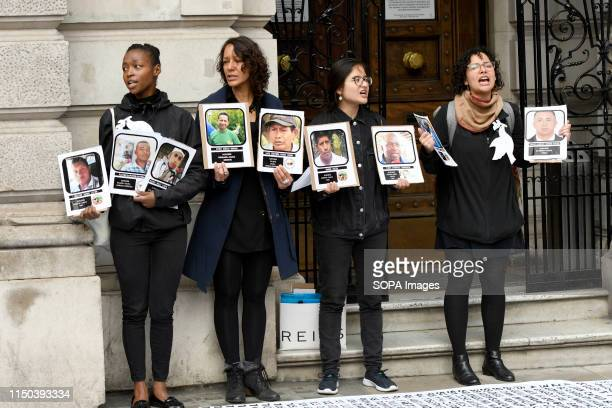 Demonstrators hold placards with photos of social leaders killed in Colombia during the protest Demonstrators gathered outside Gibson Hall to protest...