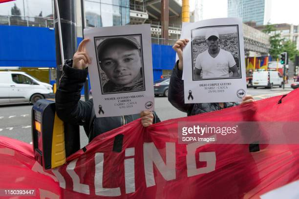 Demonstrators hold placards with the photos of social leaders killed in Colombia during the protest Demonstrators gathered outside Gibson Hall to...