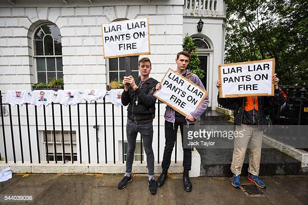 Demonstrators hold placards with the words 'Liar Liar Pants On Fire' written on them as they protest next to underwear featuring various politicians...