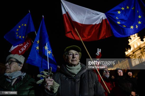 Demonstrators hold Polish and European Union flags during a protest against the recently signed judiciary law by the Polish President Andrezj Duda at...