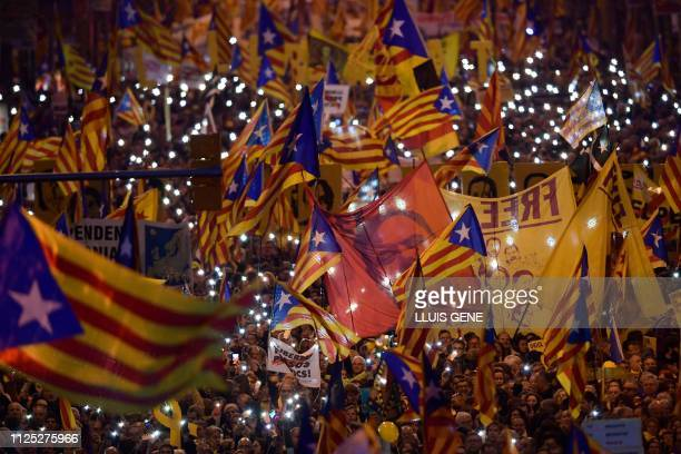 TOPSHOT Demonstrators hold portraits of jailed Catalan separatist Oriol Junqueras and wave Catalan proindependence Estelada flags during a protest...