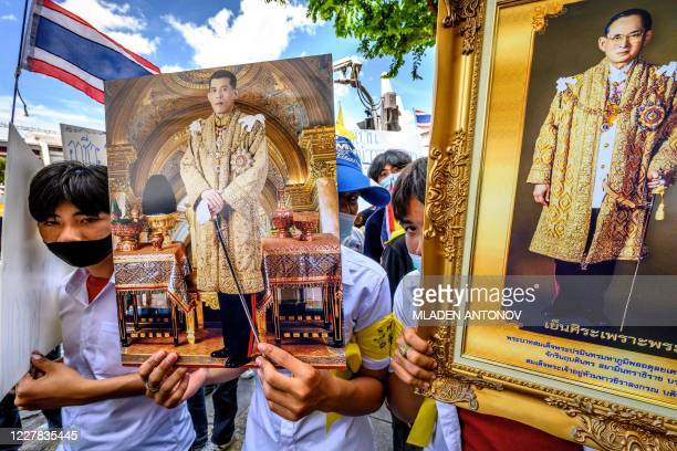 Demonstrators hold portraits of Thailand's King Maha Vajiralongkorn and his late father king Bhumibol Adulyadej during a pro-government and...