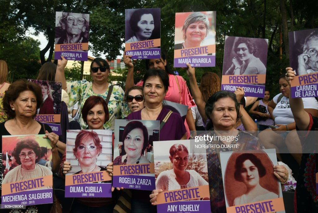 demonstrators hold portraits of women victims of violence during a