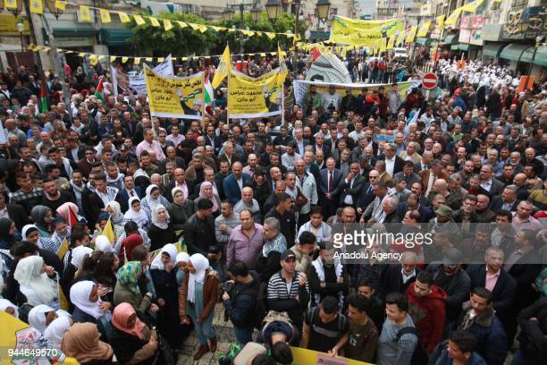 Demonstrators hold posters and flags during a demonstration in support of Palestinian President Mahmoud Abbas on April 11 2018 in Tulkarem West Bank