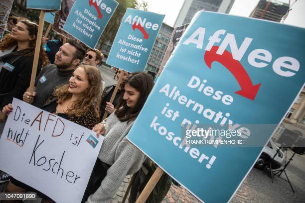 Demonstrators hold posters and placards reading AfNeee This alternative is not kosher as they take part in a rally organised by Germany's JSUD Jewish...