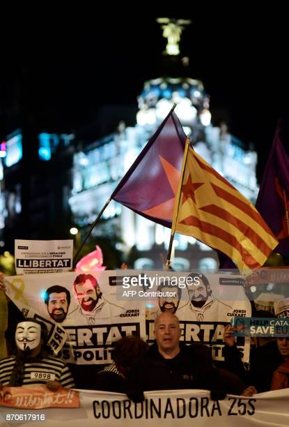 Demonstrators hold posters demanding 'Freedom for political prisoners' with pictures of detained leaders of Catalan separatist groups Jordi Cuixart...