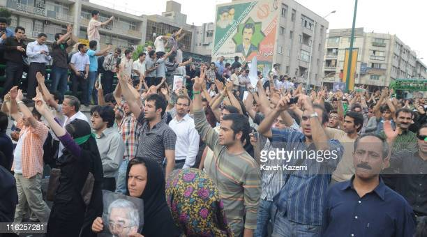 Demonstrators hold posters of Mir Hossein Mousavi, the defeated presidential candidate, while on a march towards Azadi Square, Tehran, 15th June...
