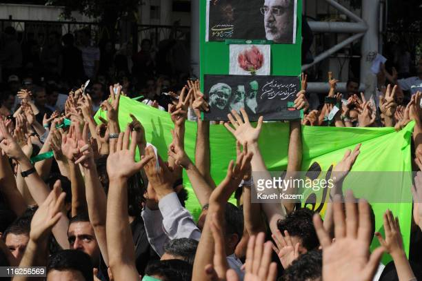 Demonstrators hold posters of Mir Hossein Mousavi the defeated presidential candidate while marching towards Azadi Square Tehran 15th June 2009 The...