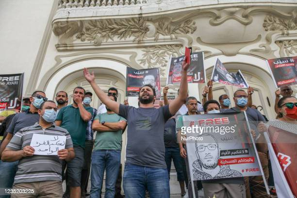 Demonstrators hold posters of Yassine Ayari that read free Yassine Ayari, as a protester raising a copy of the Tunisian constitution gestures and...