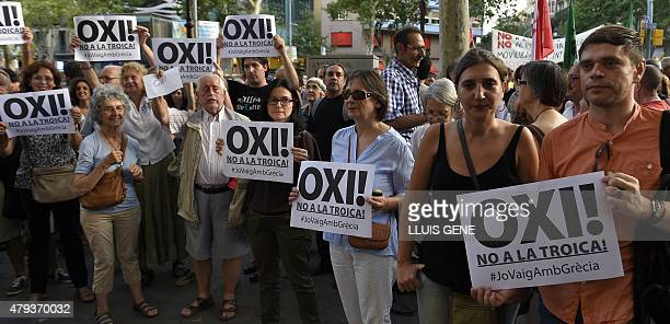 Demonstrators hold posters supporting Greece and against the Troika as they protest in front of the European Commission headquarters in Barcelona...