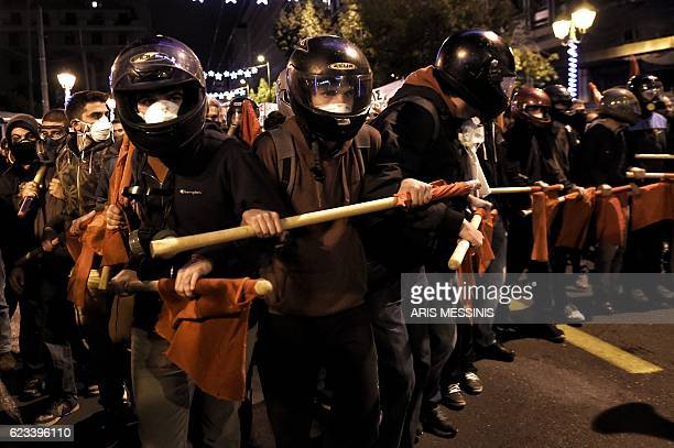 TOPSHOT Demonstrators hold red flags during a protest against the visit of the US president in Athens on November 15 2016 US President Barack Obama...