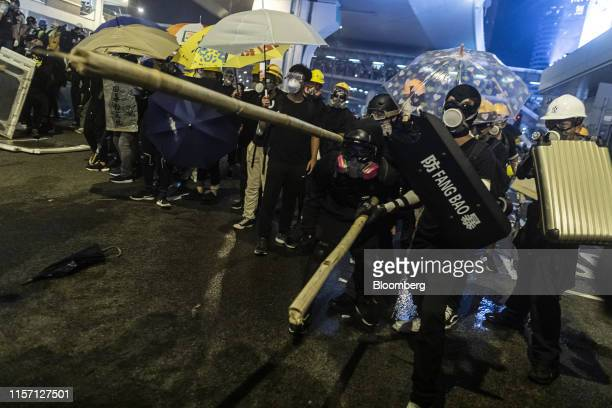 Demonstrators hold shields and bamboo sticks as they stand off against riot police during a protest in the Sheung Wan district of Hong Kong China on...