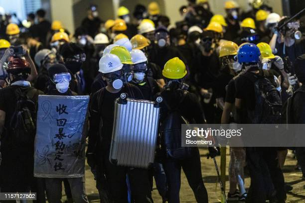 Demonstrators hold shields as they stand off against riot police during a protest in the Sheung Wan district of Hong Kong China on Sunday July 21...