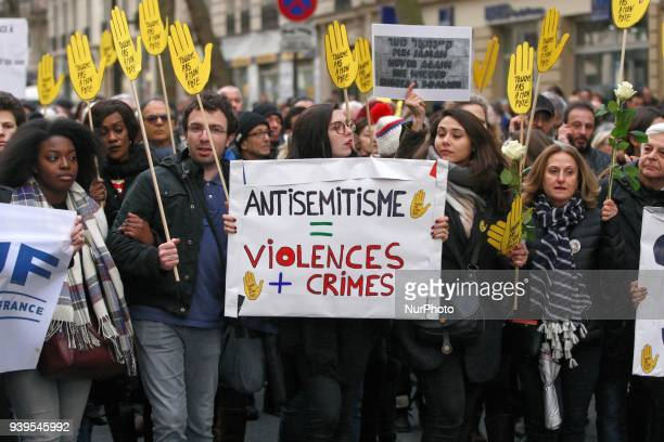 Demonstrators hold signs against antiSemitism during a silent march in Paris on March 28 in memory of Mireille Knoll an 85yearold Jewish woman...