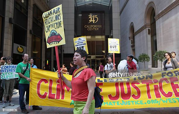 Demonstrators hold signs and a banner in fornt of the offices of Chevron Corp as they protest the climate and energy bill that is currently before...