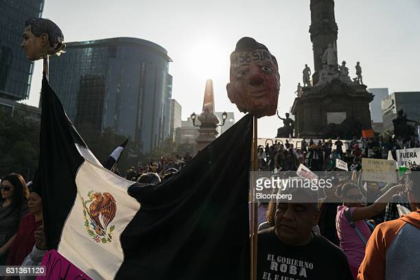 Demonstrators hold signs and a Mexican flag with masks in the likeness of Enrique Pena Nieto Mexico's president during a protest against the gasoline...