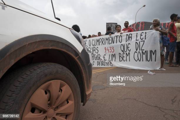 Demonstrators hold signs and block a road during a protest against Norsk Hydro ASA discharging untreated water into a nearby river in front of the...