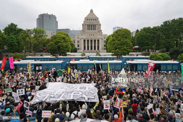 Demonstrators hold signs and chant slogans during a protest against Japans Prime Minister Shinzo Abe outside the National Diet building in Tokyo,...