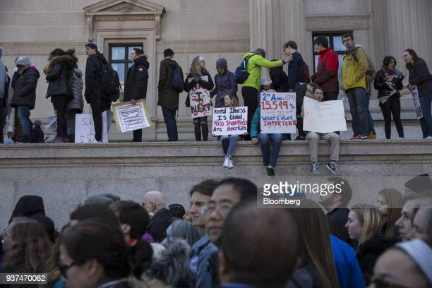 Demonstrators hold signs and gather on Pennsylvania Avenue during the March For Our Lives in Washington DC US on Saturday March 24 2018 Thousands of...