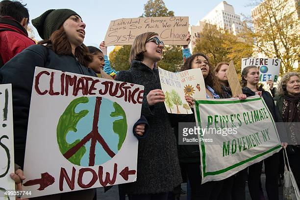 Demonstrators hold signs and participate in a collective chant at the close of the march On the eve of the Paris Climate Summit environmental...