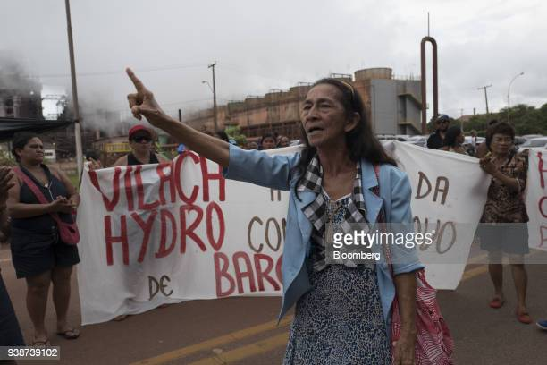 Demonstrators hold signs and shout slogans during a protest against Norsk Hydro ASA discharging untreated water into a nearby river in front of the...