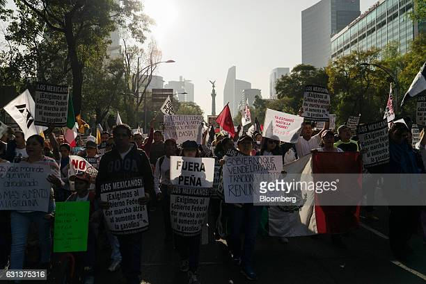 Demonstrators hold signs as they march during a protest against the gasoline price hike in Mexico City Mexico on Monday Jan 9 2017 The government is...
