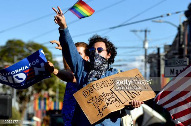 Demonstrators hold signs as they party and dance in the street after after Joe Biden was declared the winner of the 2020 presidential election on...