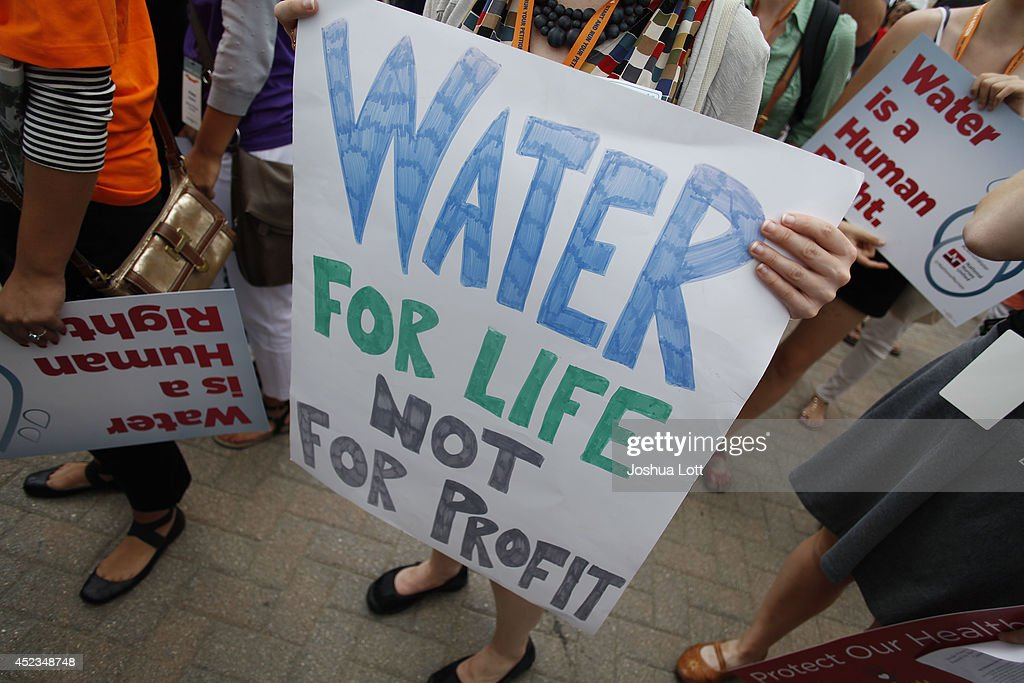 Demonstrators hold signs as they protest against the Detroit Water and Sewer Department July 18, 2014 in Detroit, Michigan. The Detroit Water and Sewer Department have disconnected water to thousands of Detroit residents who are delinquent with their bills.