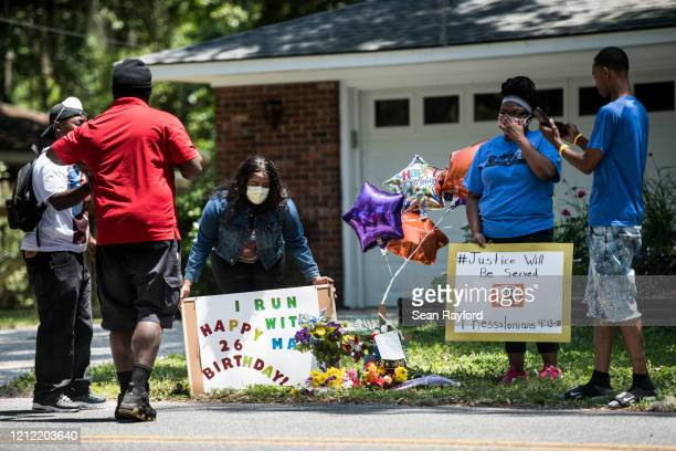 Demonstrators hold signs at a memorial for Ahmaud Arbery near where he was shot and killed May 8, 2020 in Brunswick, Georgia. Gregory McMichael and...