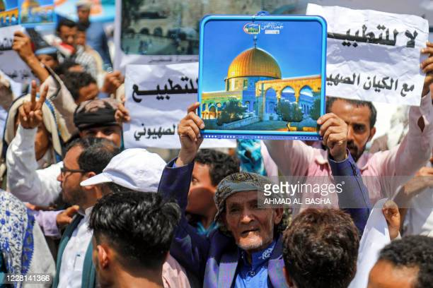 """Demonstrators hold signs depicting Jerusalem's Dome of the Rock alongside other signs reading in Arabic """"no to normalisation with the Zionist..."""
