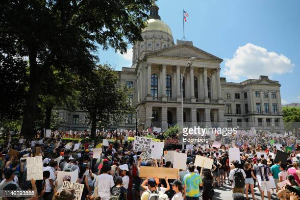 Demonstrators hold signs during a protest against Georgia's heartbeat abortion bill outside of the Georgia State Capitol building in Atlanta Georgia...