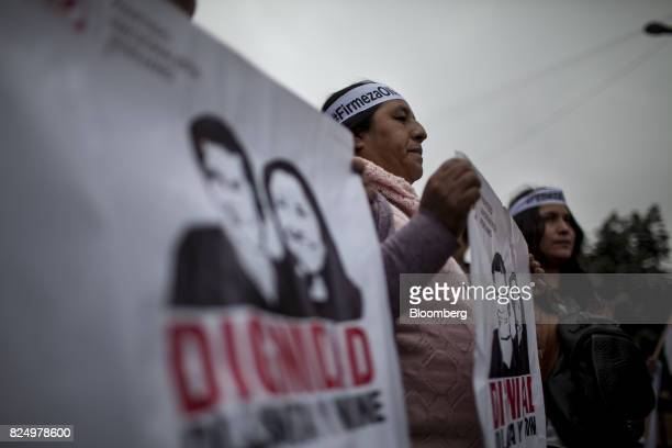 Demonstrators hold signs during a protest against the detention of former Peruvian President Ollanta Humala and his wife Nadine Heredia outside the...