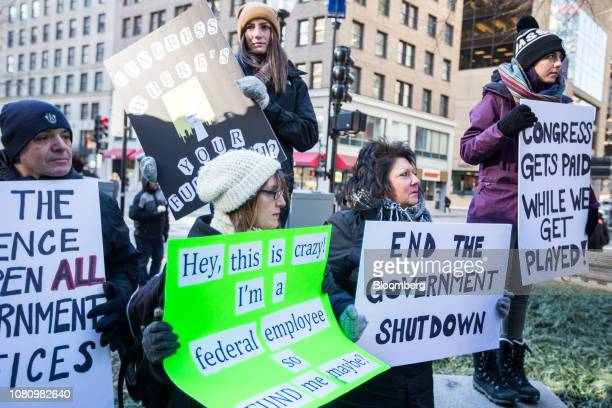 Demonstrators hold signs during a protest against the government shutdown in Boston Massachusetts US on Friday Jan 11 2019 The...