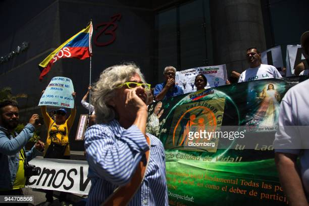 Demonstrators hold signs during a protest against the government's handing of medicine shortages in Caracas Venezuela on Monday April 9 2018 The...